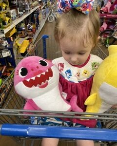 Sophia holding pink baby shark plush
